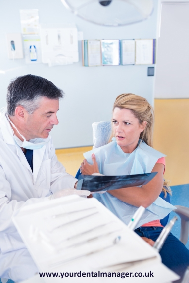 Dentist discussing x-ray with his patient